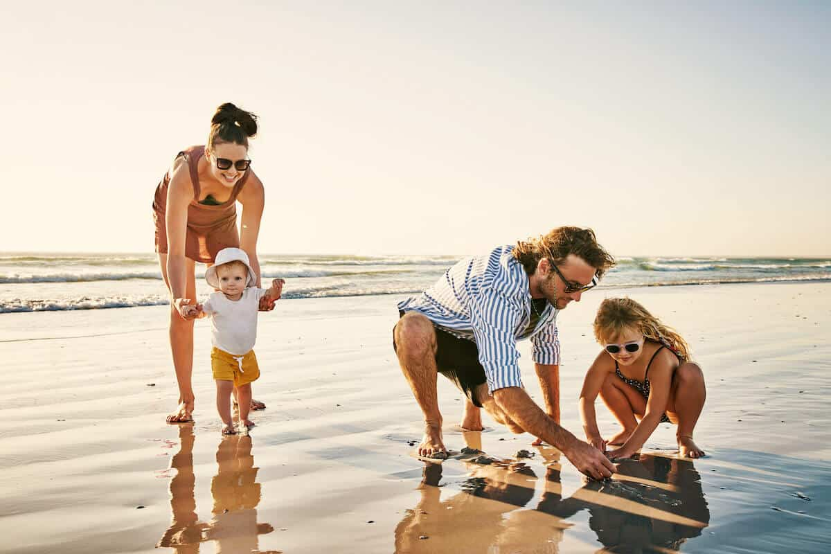mum, dad and 2 children playing on a beach